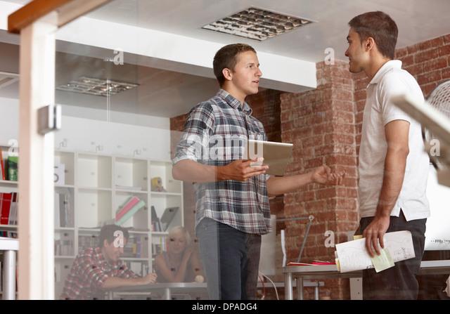 Männlichen Kollegen mit digital-Tablette in modernen Büro Stockbild