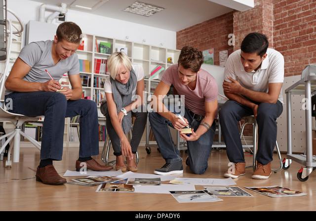 Kolleginnen und Kollegen treffen, Blick auf Papiere auf Etage Stockbild