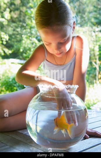 Junges Mädchen mit den Fingern im Goldfischglas Stockbild