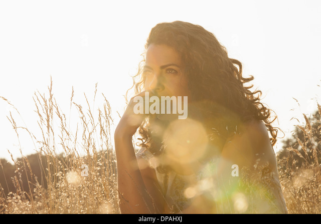 Frau sitzt zwischen wilden Blumen Stockbild