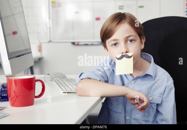 Junge mit Klebstoff Hinweis für Mund, Zeichnung der Schnurrbart Stockbild