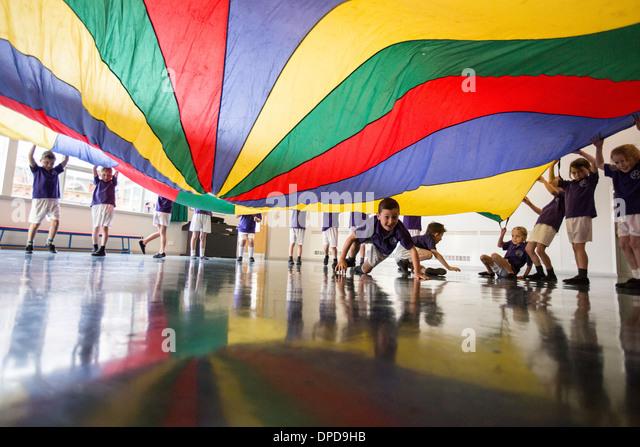 Schülerinnen und Schüler an einer UK-Grundschule spielen mit einem Fallschirm in der Aula Stockbild