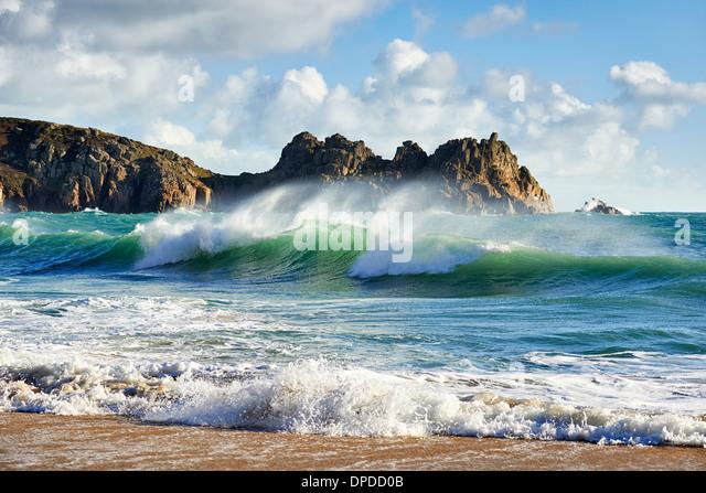 Eine Curling-Welle bricht am schönen Porthcurno beach Stockbild