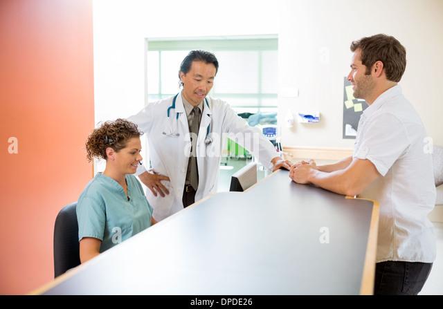 Ärzteteam arbeiten am Computer beim Mann stehen an der Rezeption Stockbild