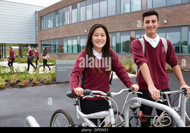 Teenager-Freunde mit Zyklen außerhalb der Schule Stockbild