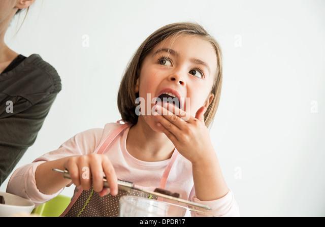 Mädchen lecken Teig von Fingern Stockbild