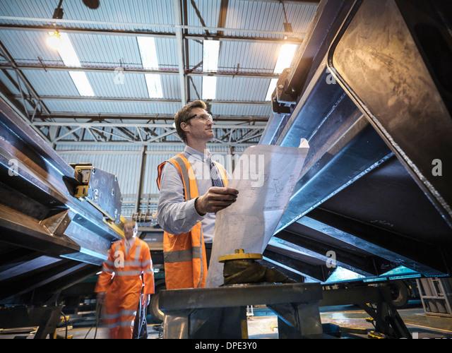 Ingenieur mit Konstruktionszeichnungen in Fabrik Stockbild