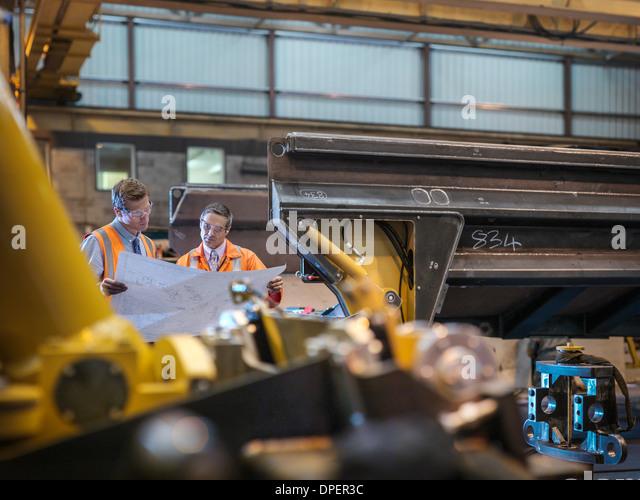 Ingenieure prüfen technische Zeichnungen zusammen in Fabrik Stockbild