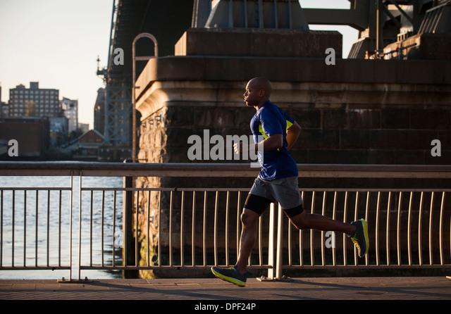 Mann, jogging am Bürgersteig Stockbild