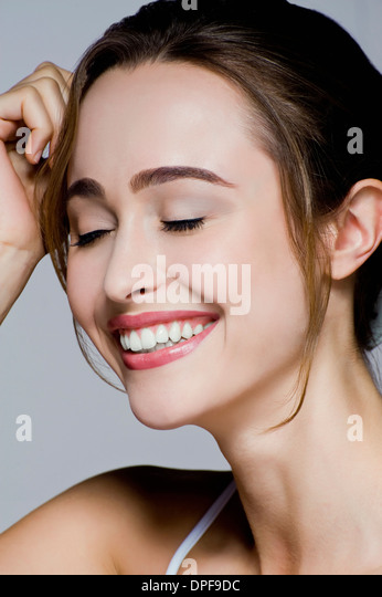 Studio-Porträt der jungen lächelnde Frau mit Augen geschlossen Stockbild