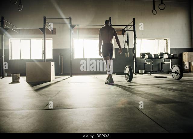 Junger Mann Übungsstange im Gymnasium vorbereiten Stockbild