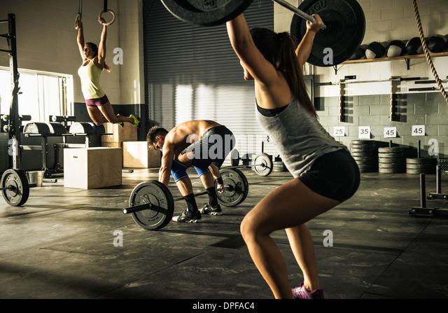 Menschen, die training mit Hanteln und Gymnasium Ringe Stockbild
