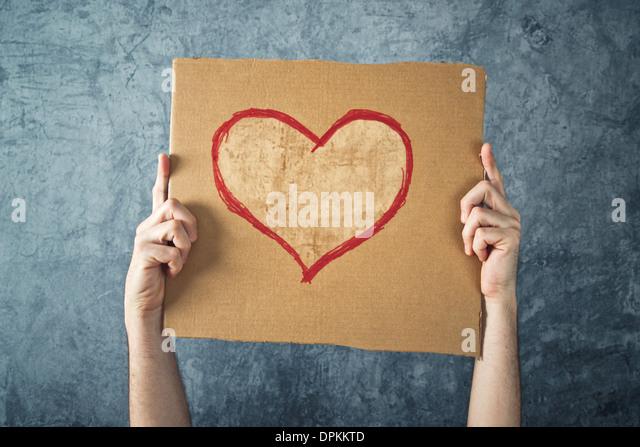 Mann, der Pappe mit Herzform Zeichnung als Valentinstag Konzeptbild hält. Stockbild