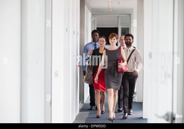Einige Geschäftsleute, die entlang eines Korridors in Richtung der Kamera Stockbild