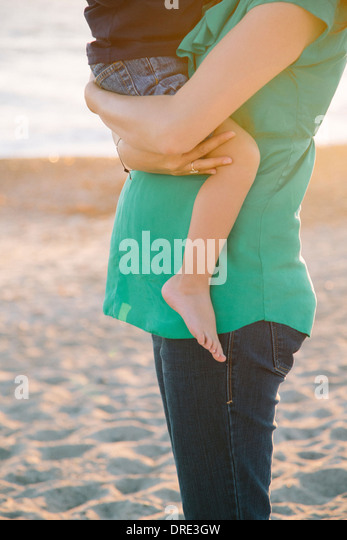 Schwangere Frau halten junge am Strand Stockbild