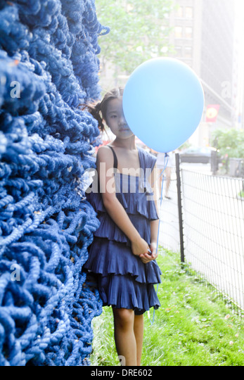 Junge asiatische Mädchen im blauen Kleid mit Ballon Stockbild