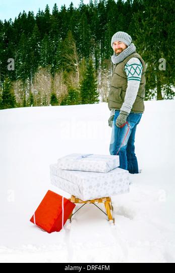 Man zieht Geschenke auf Schlitten, Spitzingsee, Bayern, Deutschland Stockbild