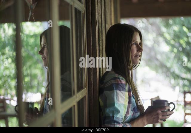 Utah USA Frau mit schwarzen Haaren Veranda halten Tasse Kaffee Stockbild