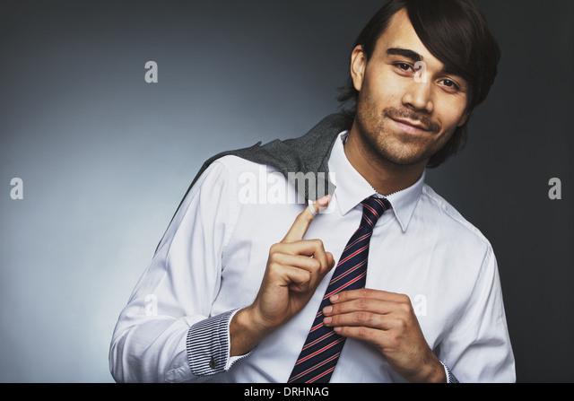 Porträt von gut aussehend männlichen Unternehmer hält seinen Mantel über die Schulter schauen Stockbild