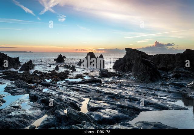 Ebbe und Sonnenaufgang am Strand von Looe in Cornwall Stockbild
