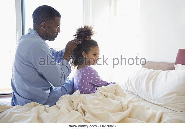 Vater macht Pferdeschwanz in Mädchen Haare Stockbild