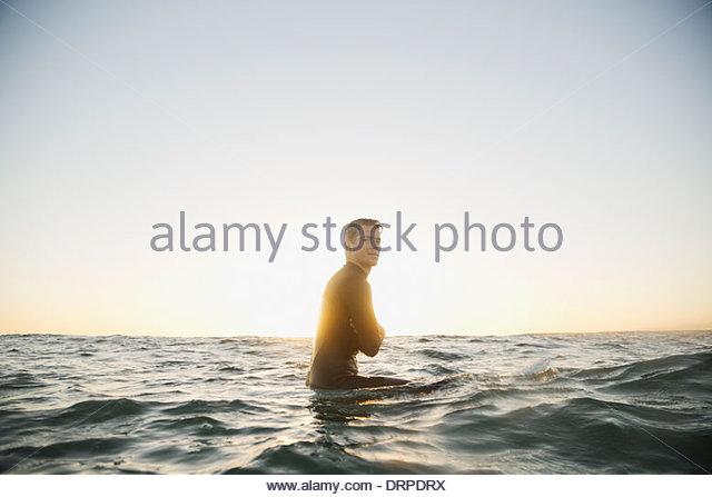 Portrait der Mann sitzt auf Surfbrett Stockbild