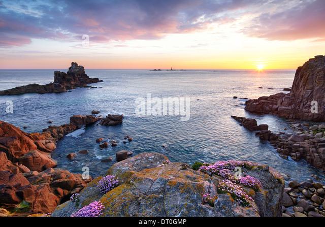 Die untergehende Sonne am Ende des Landes mit Sparsamkeit klammerte sich an den Felsen. Stockbild