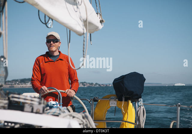 Washington State USA mittleren Alter Mann Lenkung Segelboot am Puget Sound Stockbild