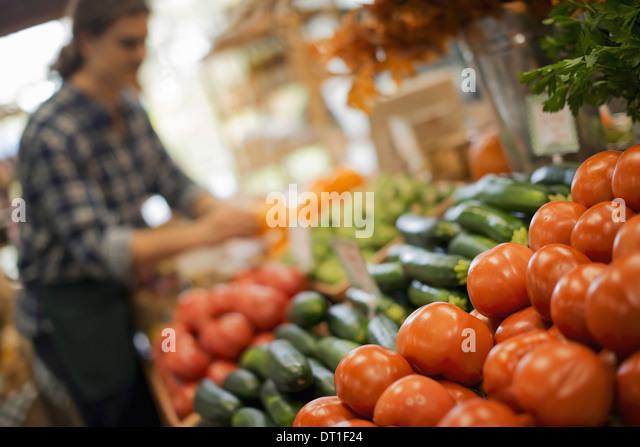Bio-Landwirt Arbeit A jungen Mann arrangieren eine Anzeige von frischen Produkten auf einem Bauernhof stehen, Tomaten Stockbild