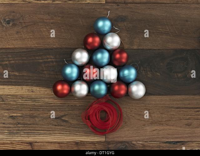 Sammlung von blau rot-silbernen Ornamenten angeordnet in Form eines dreieckigen Weihnachtsbaum mit einem roten Band Stockbild