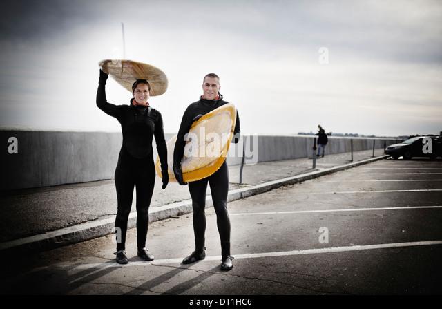 Ein Surfer in einen Neoprenanzug auf einem Parkplatz Stockbild