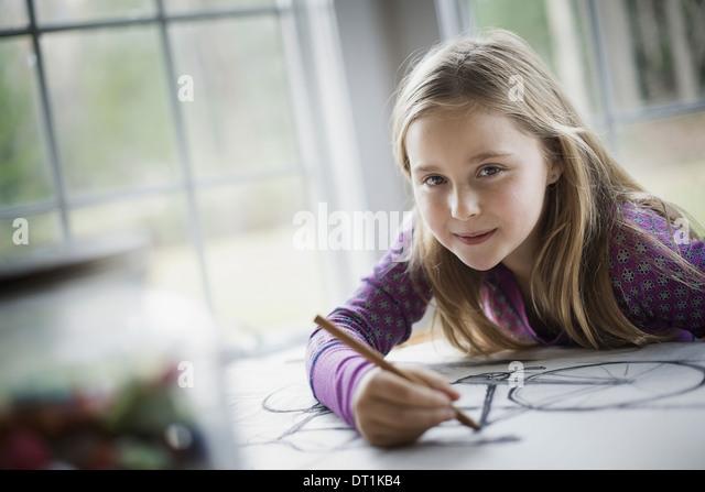 Eine Familie zu Hause ein Kind sitzt an einem Tisch mit Hilfe eines Bleistifts und die Schaffung einer Strichzeichnung Stockbild