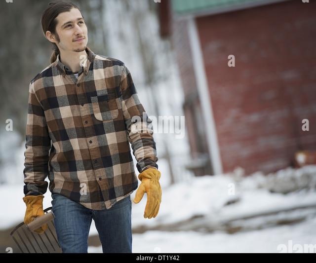 Ein Bio-Bauernhof im Winter in New York State USA A Mann im karierten Hemd zu Fuß über schneebedeckten Stockbild