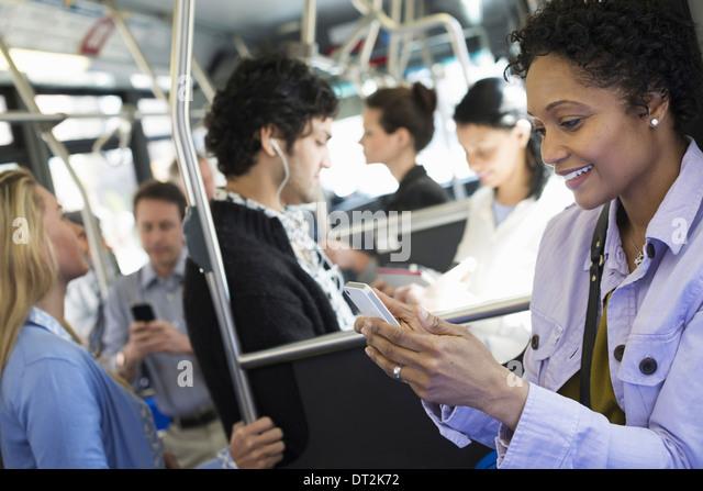 New York City Männer und Frauen Bus ÖPNV in Kontakt zu bleiben, eine junge Frau überprüfen oder Stockbild