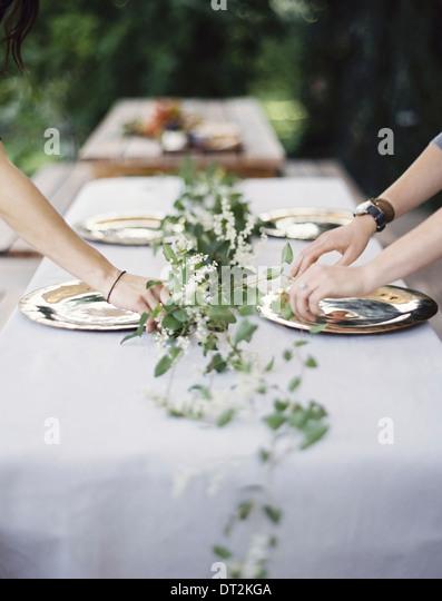 Zwei Personen, beugte sich über einen Tisch gelegt außerhalb mit einem weißen Tuch und eine zentrale Stockbild