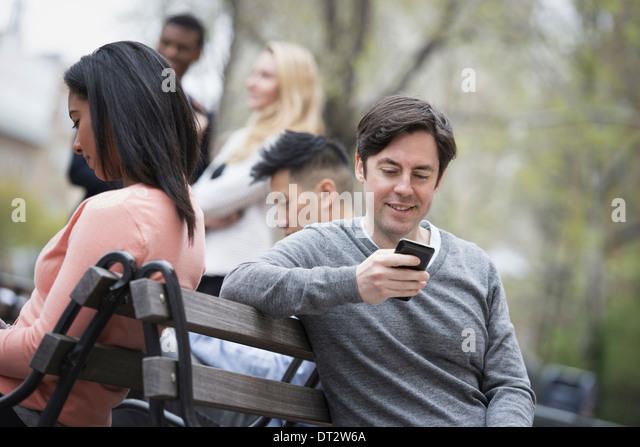Blick über Citycity Park auf einer Parkbank sitzen, fünf Menschen Männer und Frauen, die ihre Telefone Stockbild