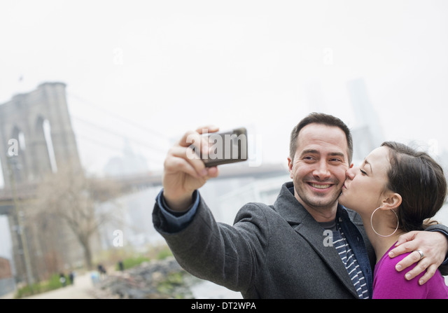 Brooklyn Bridge überqueren den East River ein paar Aufnahme eines Bildes mit einem Telefon eine selfy von sich Stockbild
