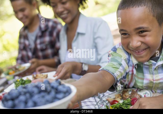 Ein Familien-Picknick in einem schattigen Waldgebiet Erwachsene und Kinder an einem Tisch sitzen Stockbild