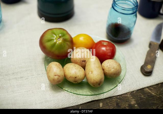 Eine Tabelle mit einem Tuch und Teller mit Kartoffeln und Tomaten Stockbild