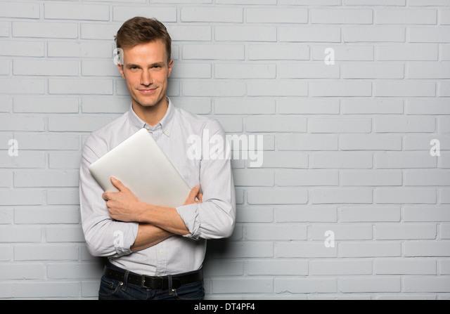 Porträt von fröhlich männlichen halten Computer, Studio grauen Hintergrund Kamera suchen Stockbild