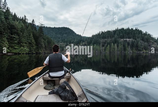 Junger Mann Angeln, Buntzen Lake, British Columbia, Kanada Stockbild