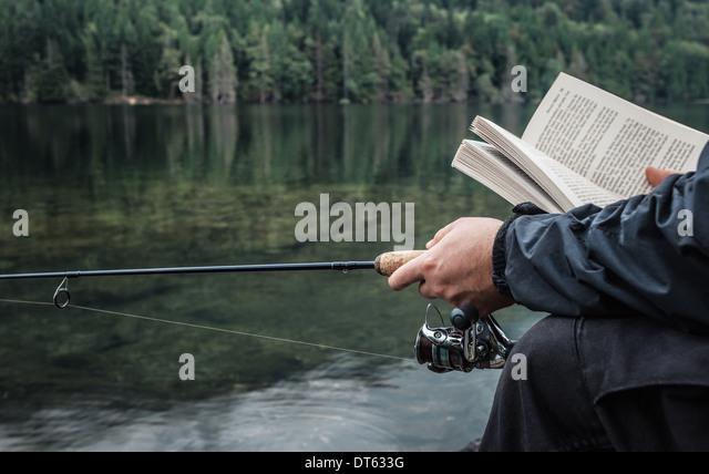 Mann Angeln mit Buch, Buntzen Lake, British Columbia, Kanada Stockbild