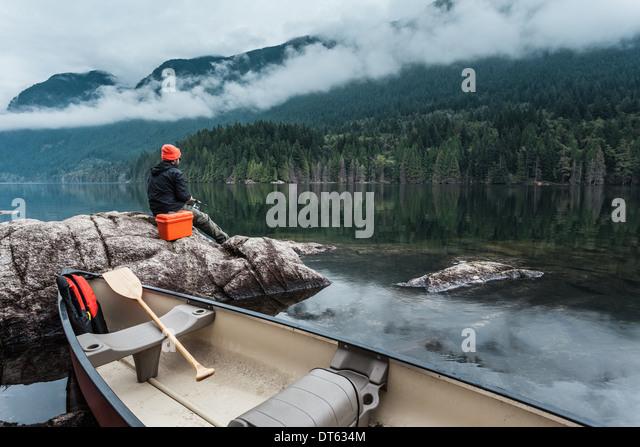 Mann Angeln vom Felsen, Buntzen Lake, British Columbia, Kanada Stockbild