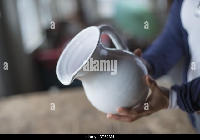 Eine Frau hält einen weißer Keramik Krug in einem antiken waren und Möbelhaus. Stockbild