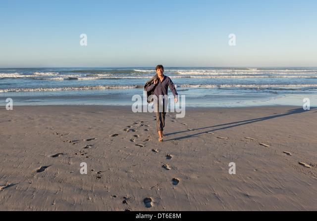 Mann zu Fuß am Strand Stockbild