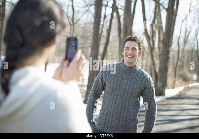 Ein paar im Freien an einem verschneiten Tag. Eine Frau mit einem Kamera-Handy Fotografieren eines Mannes. Stockbild