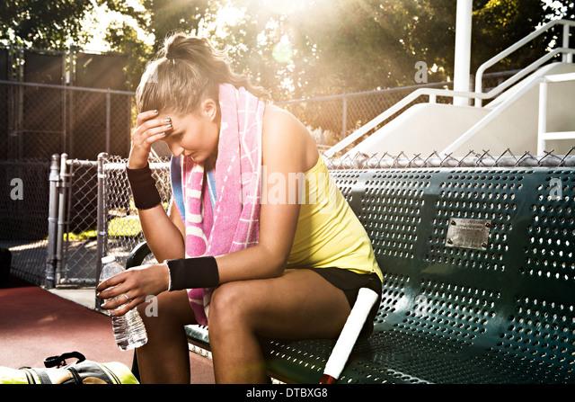 Tennisspielerin auf Bank mit Kopf in Händen Stockbild