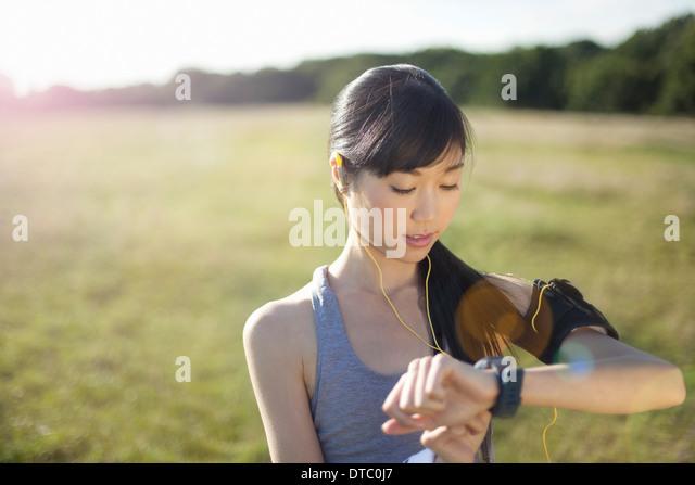 Junge weibliche Läufer Zeit Uhr gesucht Stockbild