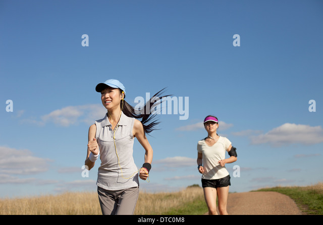 Zwei junge Frauen laufen auf Feldweg Stockbild
