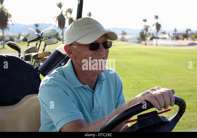 Senior männlichen Golfer Golfbuggy fahren Stockbild